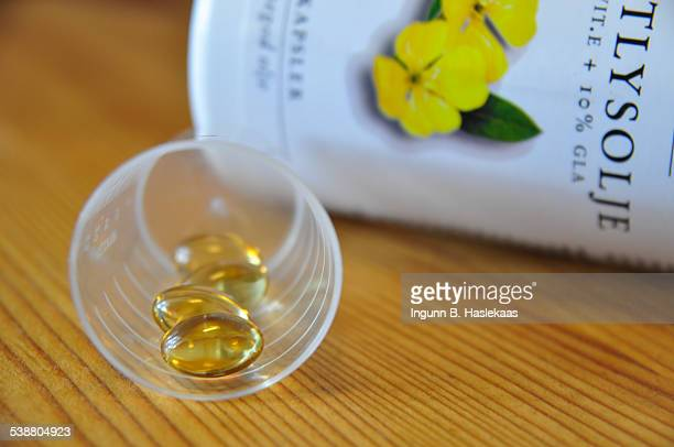 Little plastic cup with pills of Evening primrose oil and the box in the background
