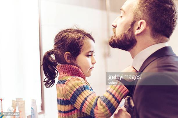 little prescholar girl binding tie to father for business outfit