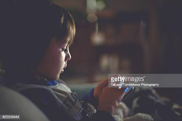 Little preschool child, playing on mobile phone on the sofa at night