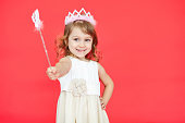 Young fairy wearing white dress and crown holding a magic wand in her hand isolated over red background
