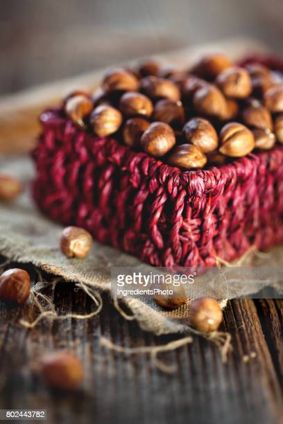 Little red basket with fresh hazelnuts on a wooden table.