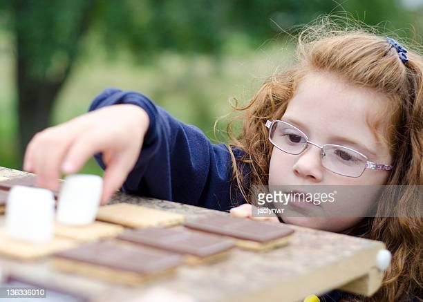 Petite fille à préparer s'mores à tête rouge
