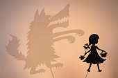 Little Red Riding Hood shadow puppet and the Big Bad Wolf's shade with the soft glowing screen of shadow theater in the background.