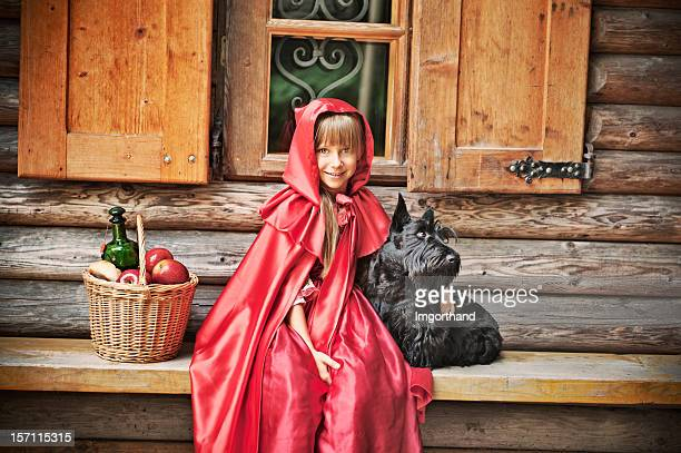 Little Red Riding Hood in front of a cottage