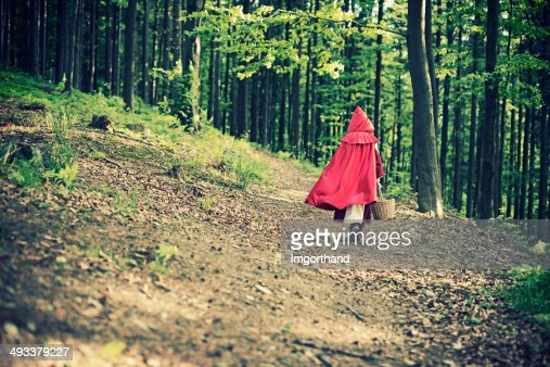 Little Red Riding Hood walking through the forest