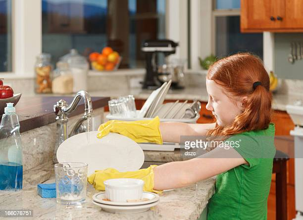little red-haired girl washing dishes in kitchen sink at home