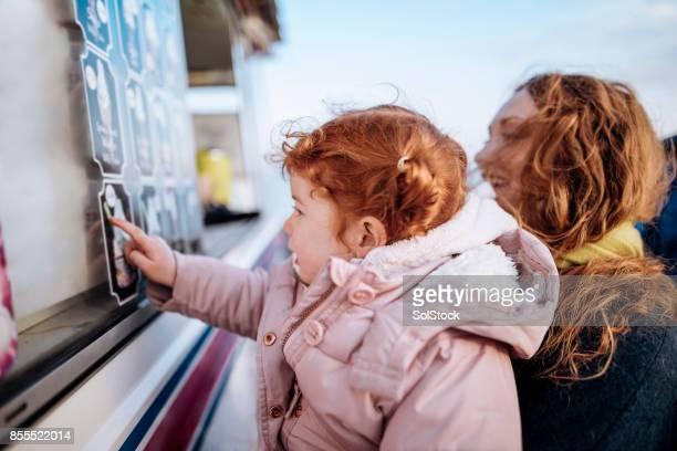 Kleine rothaarige Mädchen an einem Eiswagen
