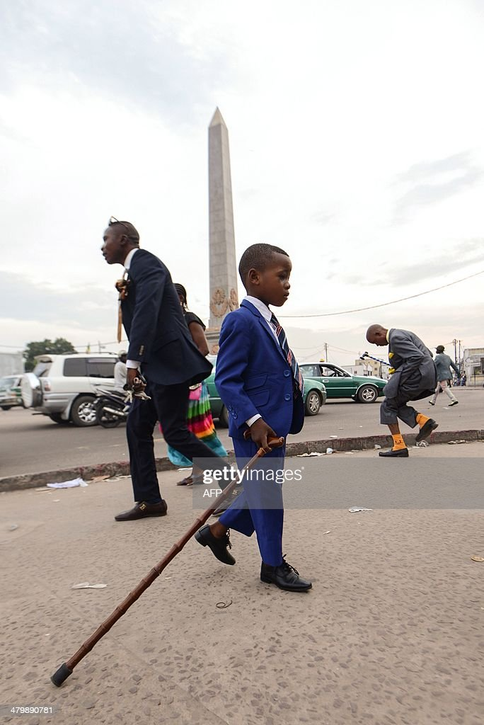 Little sapeur Prince Elvo poses with The Sapeurs Association Charle Degaule all members of the Sape Movement the acronym for 'Societe des Ambianceurs...