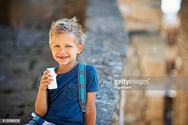 Little school boy drinking yogurt