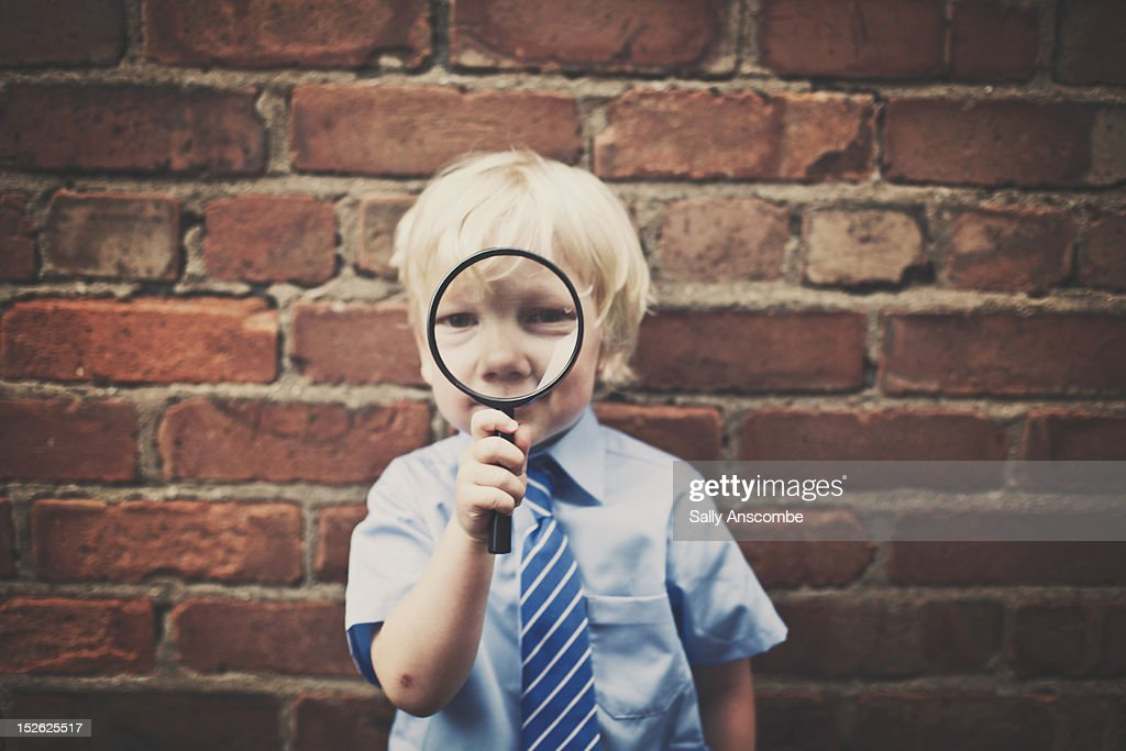 Little school boy with magnifying glass
