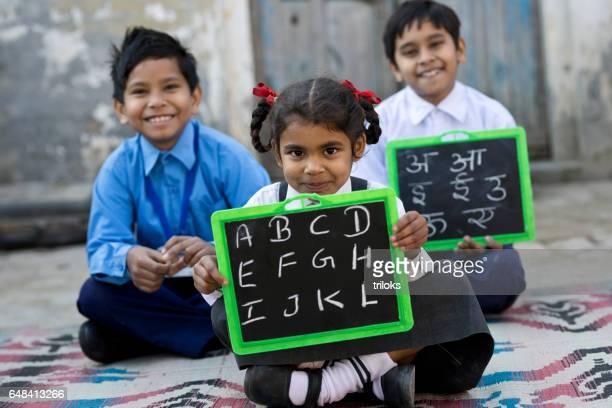 Little school children in uniform holding slate