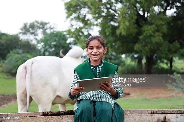 Little school girl holding digital tablet