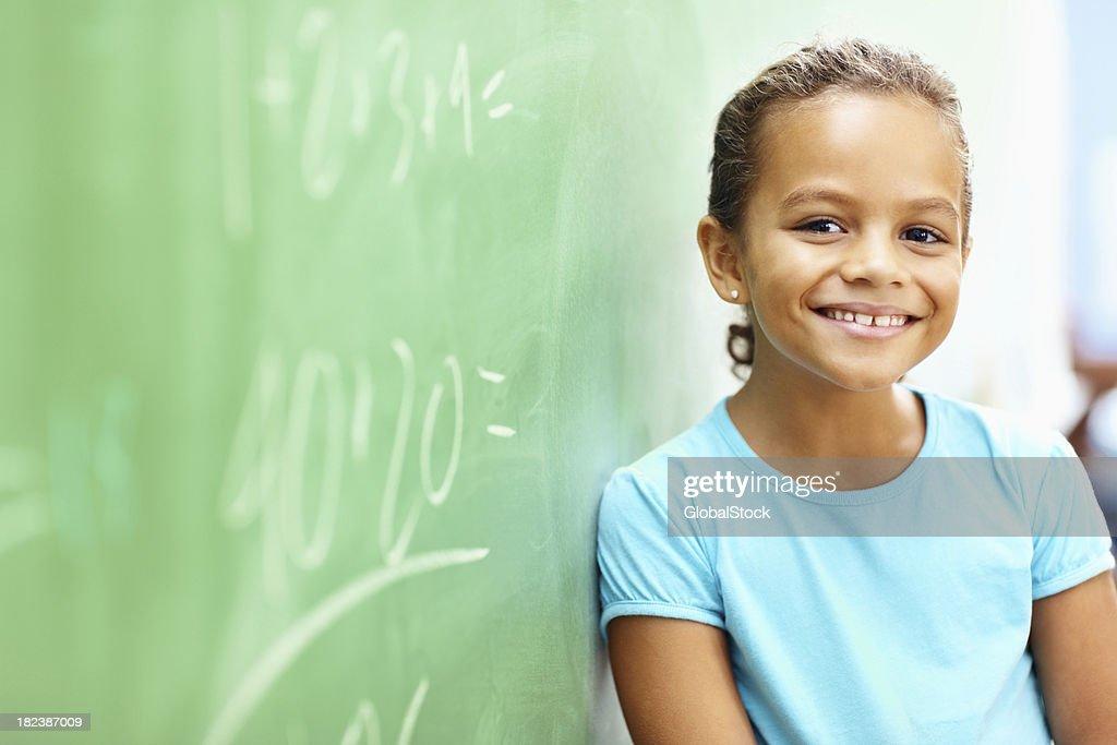 Little school girl leaning on board : Stock Photo