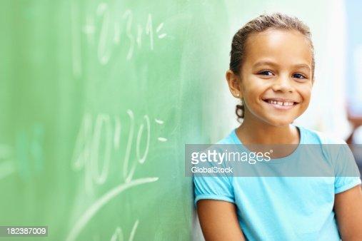 Little school girl leaning on board