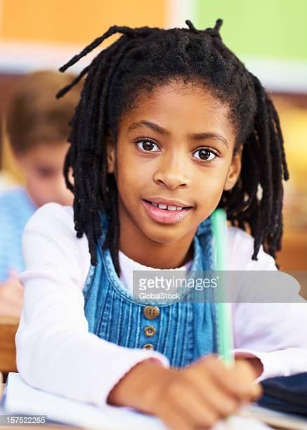 Little school girl writing an exam