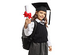 Little schoolgirl with a graduation hat and a diploma isolated on white background
