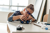 Young girl building a robotic car