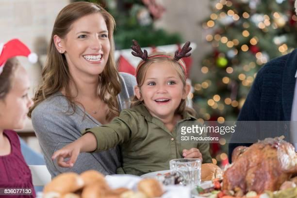 Kleine Schwester neckt große Schwester während Weihnachtsessen
