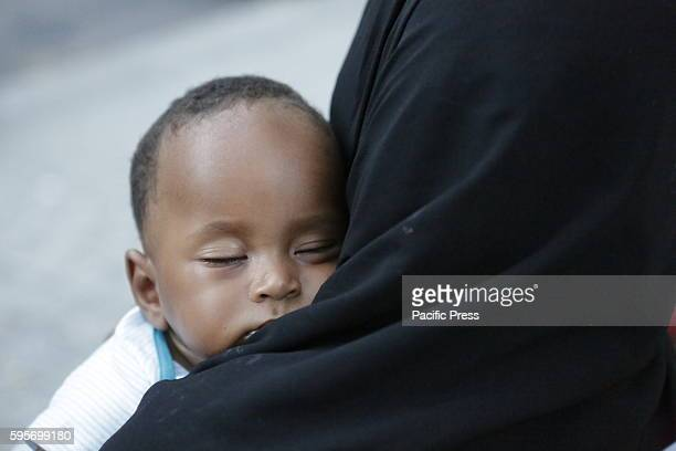A little six month old Sudanese baby boy is sleeping on the shoulder of his mother Hundreds of refugees are sleeping rough in the streets around the...