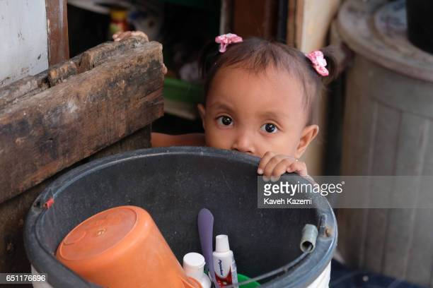 A little slum dweller girl holds on to a large plastic container used for sanitation purposes outside her makeshift home in the old town on November...
