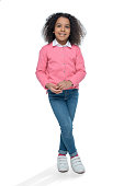 little smiling african american girl posing in pink cardigan isolated on white