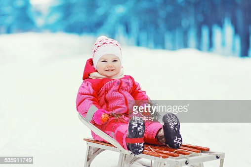 Little smiling baby sledding in the winter day : Stock Photo