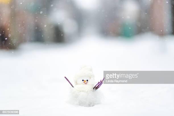A little snowman figurine under the falling snow