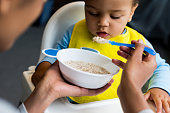 african american mother feeding little son with porridge at home