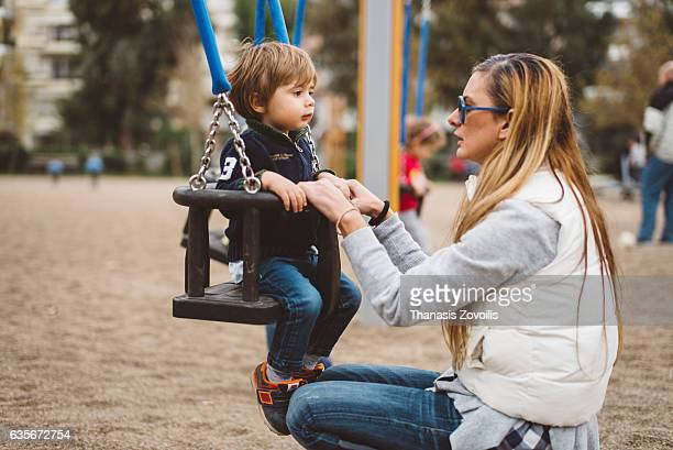 Little son swinging in park with mother