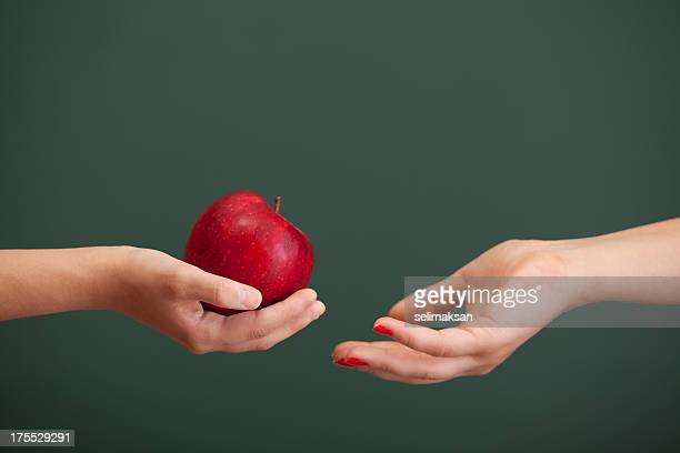 Little student hand giving red apple to teacher before blackboard