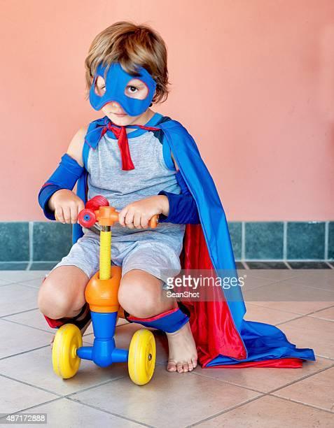 Kleine Superhelden auf einem vier Rädern Spielfahrzeug