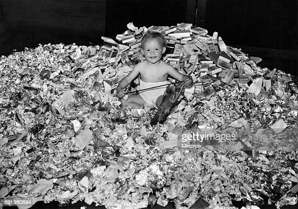 Little Susan Kemp the daugher of Arthur Kemp of the 'Denbigh arms' SW London has a huge pile of tinfoil cigarette packet to play with This was...