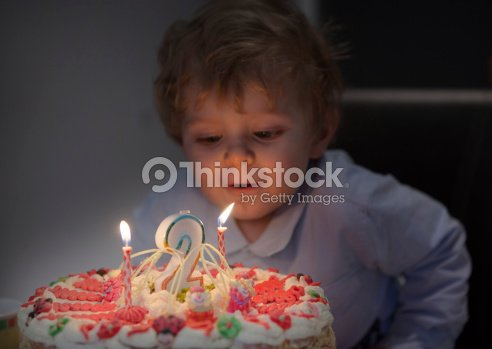 Little Sweet Toddler Blowing Candles On His 2 Birthday Cake Stock Photo