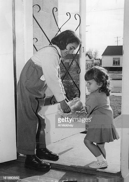 DEC 5 1956 DEC 6 1956 Little Theresa Duggan calls at the home of Denver's new Hungarian refugee family to give Erika Holubecz a doll Theresa is the...