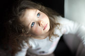 A little pretty toddler girl with blue eyes looking up seriously by the window with her eyebrows up