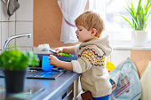 funny little blond kid boy washing dishes in domestic kitchen. Happy child having fun with helping with house work. Indoors, toddler in colorful clothes.