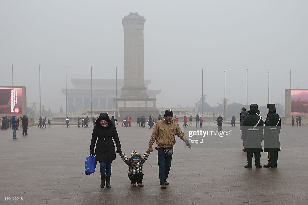 A little tourist and his parents play on the ground with frozen ice at the Tiananmen Square during severe pollution on January 31, 2013 in Beijing, China. Heavy smog that has choked Beijing for the last five days weakened slightly on Thursday due to a light rainfall, although the capital's air remains heavily polluted. The haze choking many Chinese cities covers a total area of 1.43 million square kilometers, the China's Ministry of Environmental Protection said Wednesday.