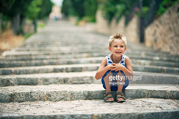 Little tourist boy sitting on Pollensa stairs
