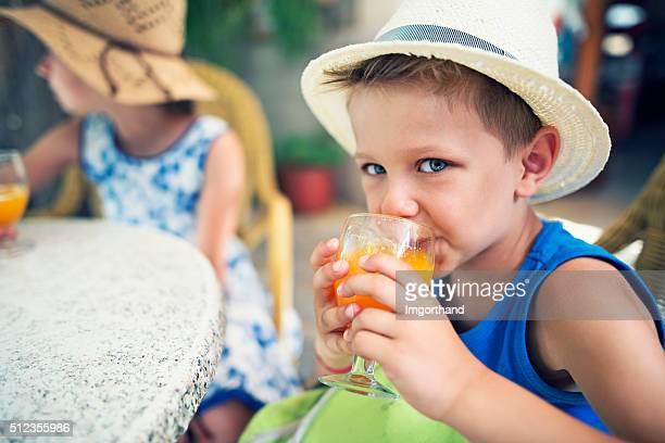 Jeunes touristes boire un verre de jus d'orange frais