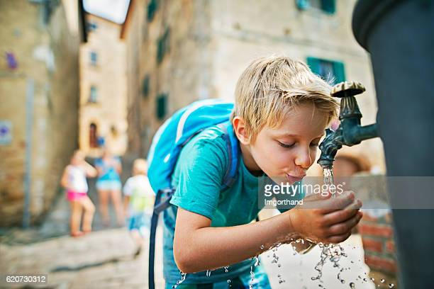 Little tourist drinking water from public fountain