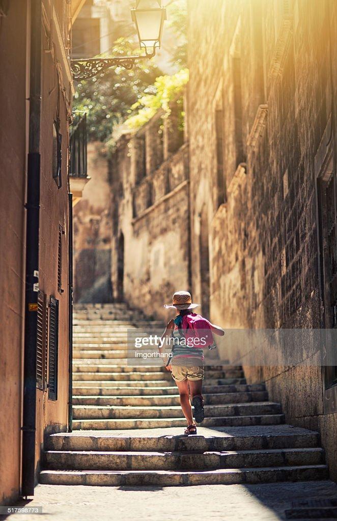 Little tourist girl visiting mediterranean town.