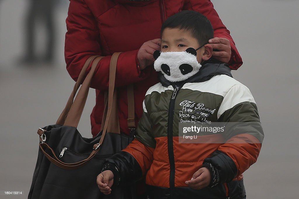A little tourist wearing a panda mask walk on the Tiananmen Square during severe pollution on January 31, 2013 in Beijing, China. Heavy smog that has choked Beijing for the last five days weakened slightly on Thursday due to a light rainfall, although the capital's air remains heavily polluted. The haze choking many Chinese cities covers a total area of 1.43 million square kilometers, the China's Ministry of Environmental Protection said Wednesday.