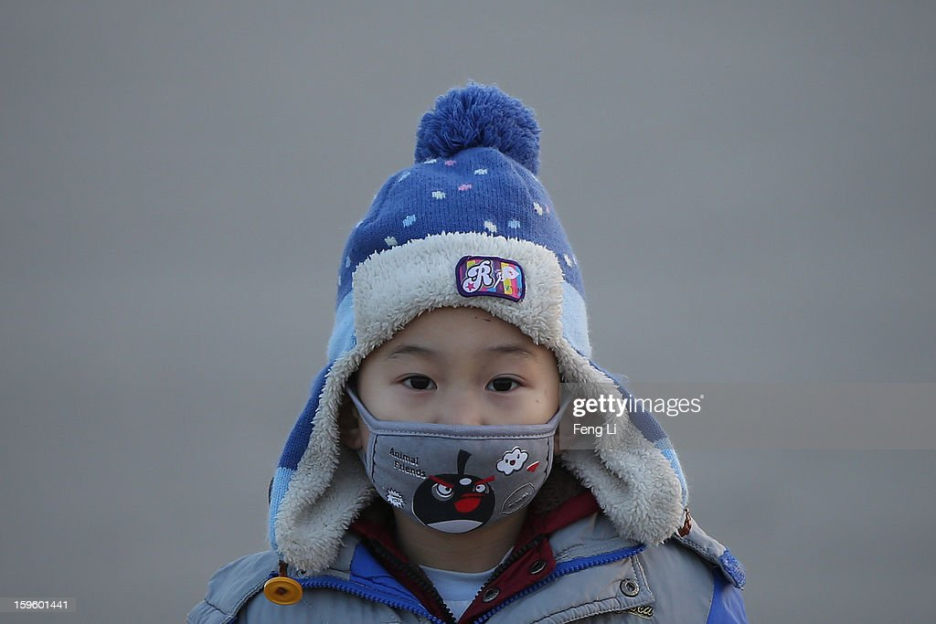 A little tourist wearing the Angry Birds mask at the Tiananmen Square during slight pollution on January 17, 2013 in Beijing, China.