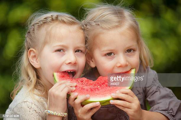 little twin girls eating melon
