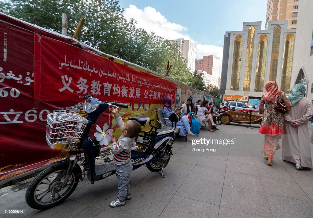 A little Uygur boy plays at roadside where there is a huge propaganda poster of compulsory education China has taken measures to protect the rights...