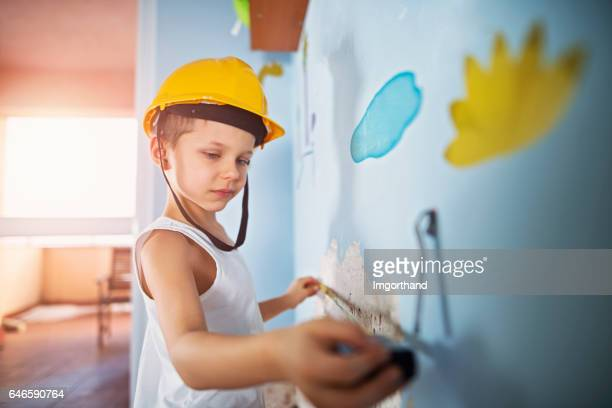Little workers measuring damaged plaster in his room