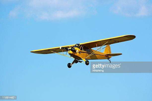 little yellow airplane Piper Cub flying in blue sky