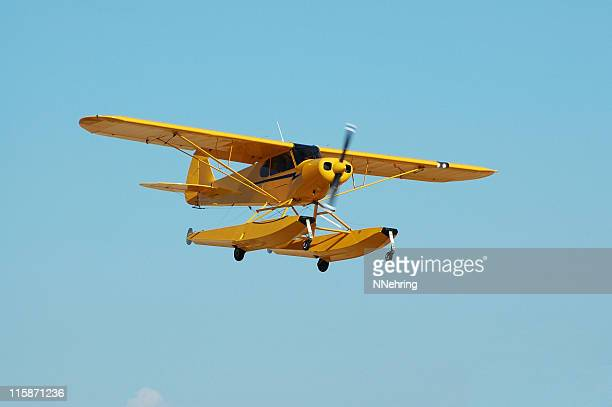 little yellow seaplane Piper Cub flying in clear blue sky