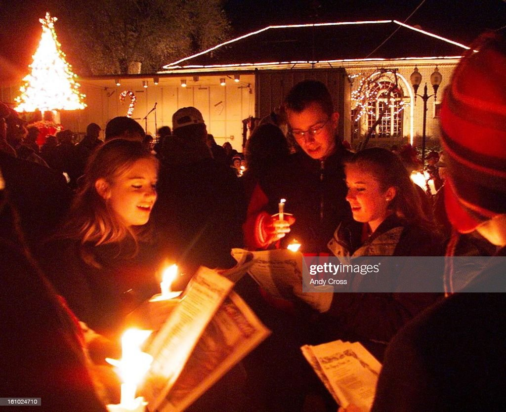 COCANDLEWALKFrom left to right Nichole Brown Dustin Bentz and Michelle Brown sing christmas carols in candle light along Main St in Littleton Friday...