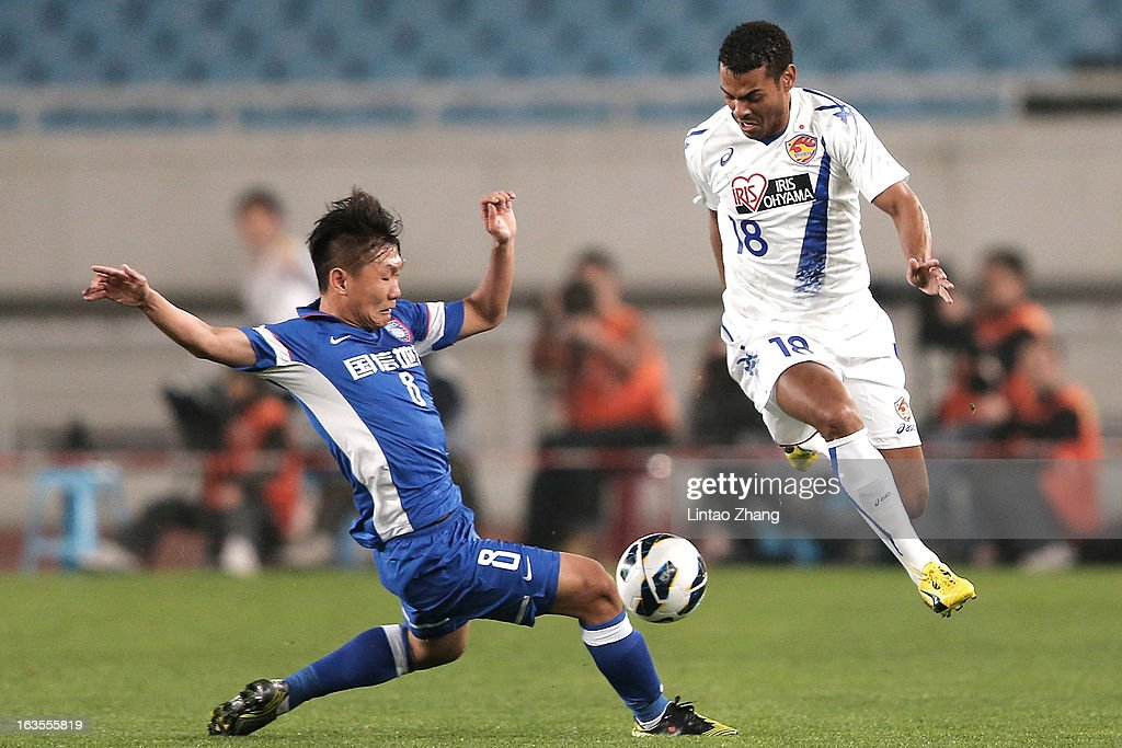 Liu Jianye (L) of Jiangsu Sainty challenges Diogo (R) of Vegalta Sendaion during the AFC Champions League match between Jiangsu Sainty and Vegalta Sendai at Nanjing Olympic Sports Center Stadium on March 12, 2013 in Nanjing, China.